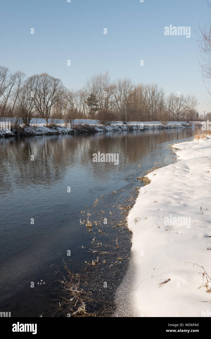 Olse river in Karvina town in Czech republic during winter day with snow and clear sky Stock Photo