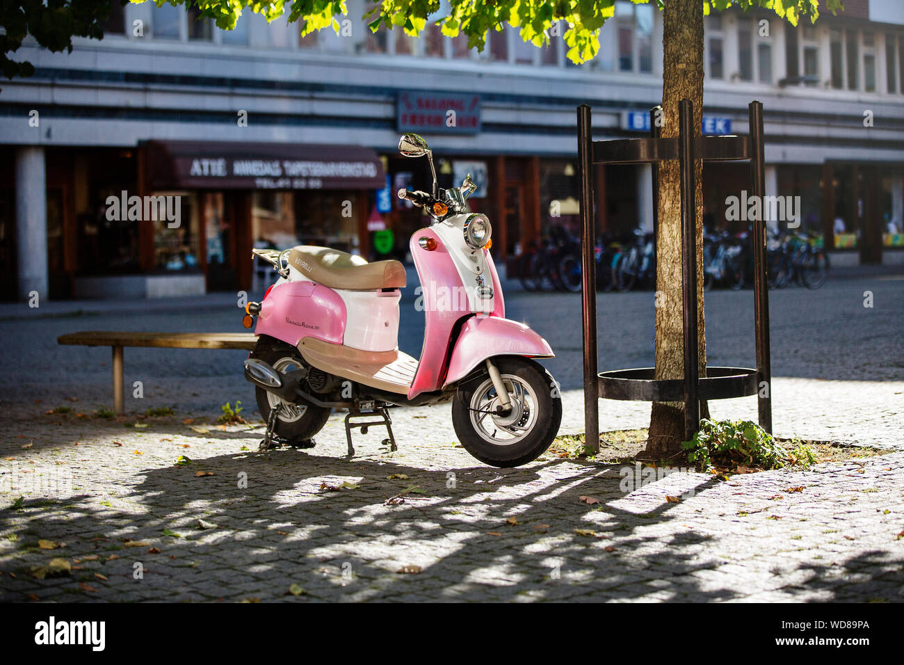 Pink scooter in public square Stock Photo