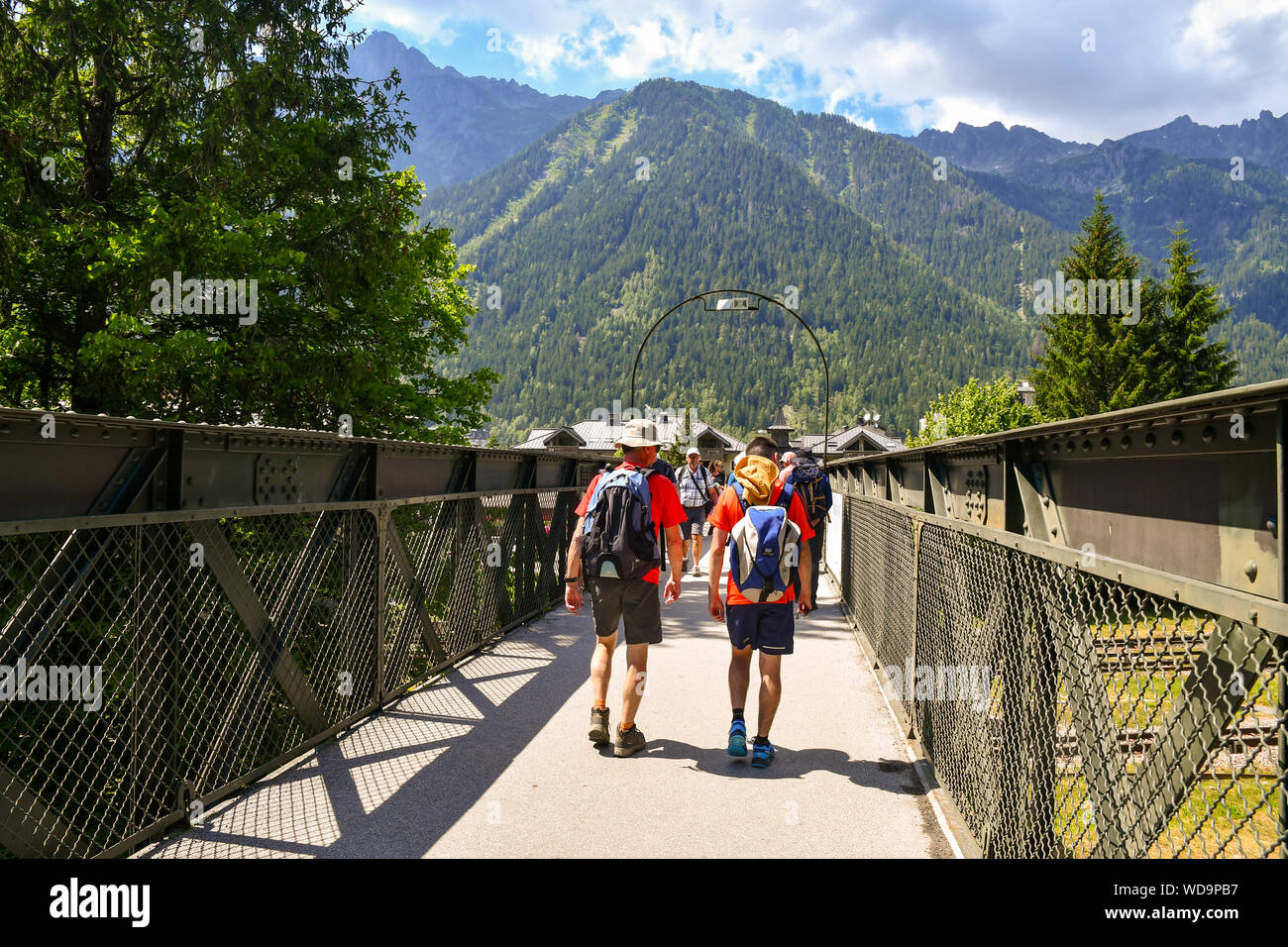 Tourists and hikers crossing a pedestrian bridge over the railway with the mountains in the background in summer, Chamonix-Mont-Blanc, Alps, France Stock Photo