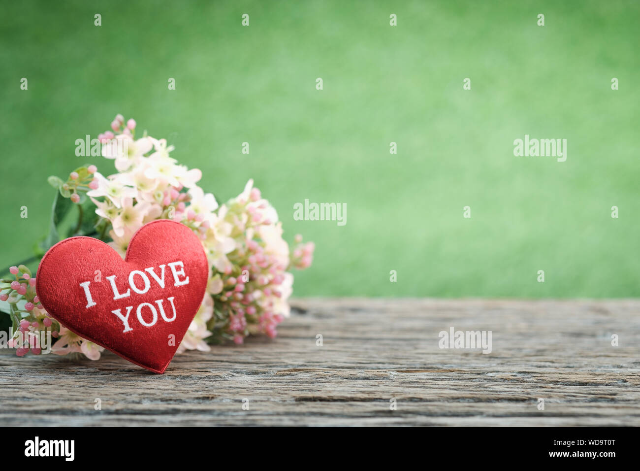 A Bouquet Of Flowers And Mini Shape Heart On A Wooden Floor In