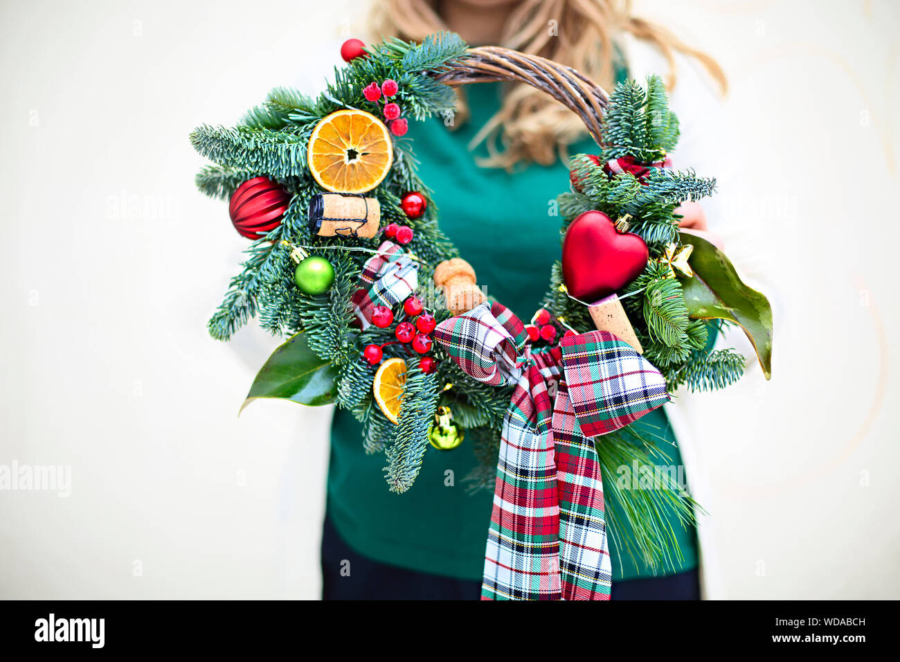 Woman holding Christmas wreath maked by herself. Close up Stock Photo