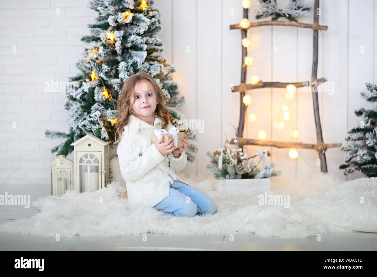 Happy little girl unpacking christmas gift at Christmas decoration Stock Photo
