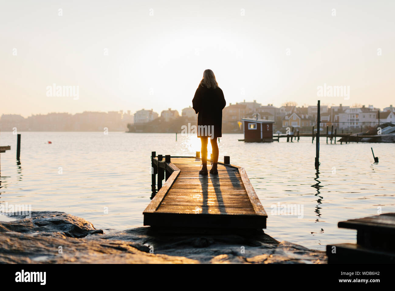 Silhouette of woman standing on jetty at sunset Stock Photo
