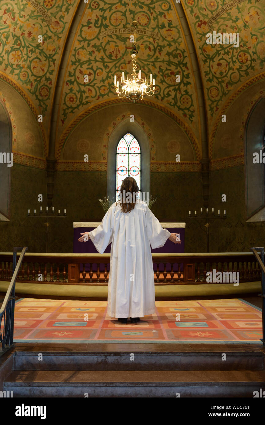 Priest In White Robes Standing At Chancel In Church Stock Photo Alamy