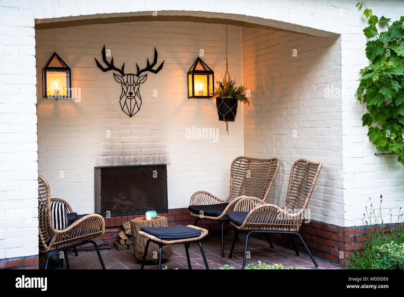 outdoor lounge set in a green garden in the alcove of a white painted building Stock Photo