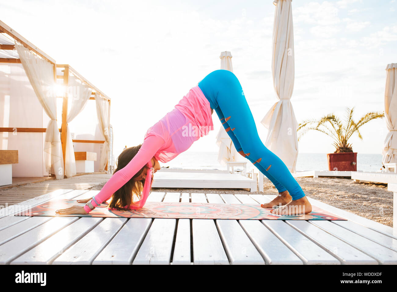 Woman doing yoga outside in a garden on a wooden floor. Stock Photo