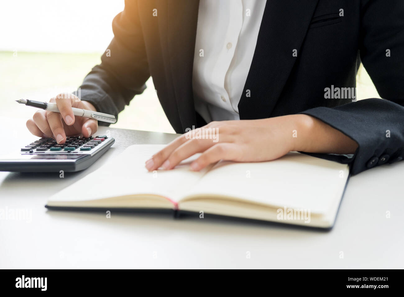 Midsection Of Businesswoman Using Calculator In Office Stock Photo