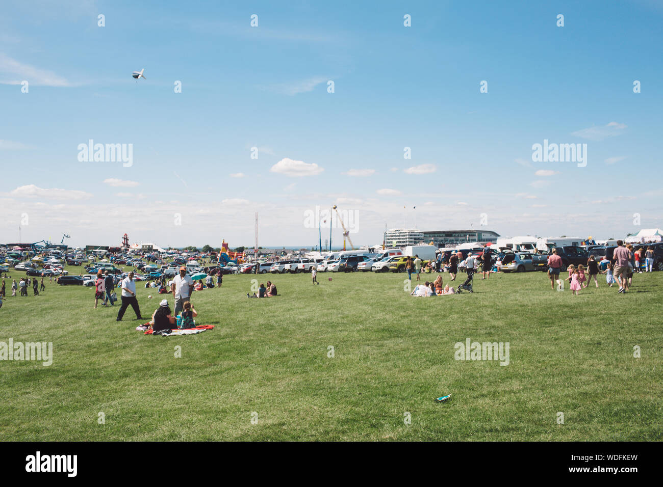 People On Field At Epsom Downs Racecourse Against Sky Stock Photo