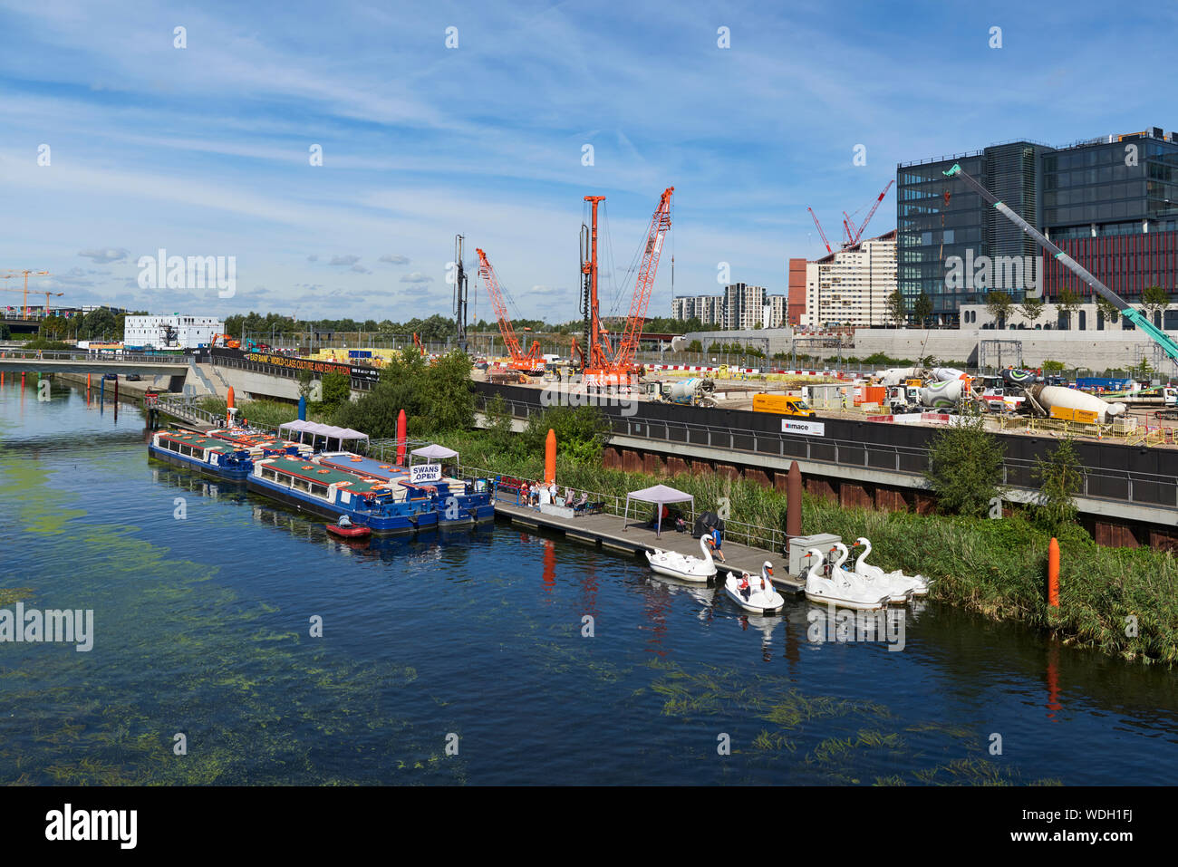 Building works by the Waterworks River, with boats, in the Queen Elizabeth Olympic Park at Stratford, East London UK Stock Photo