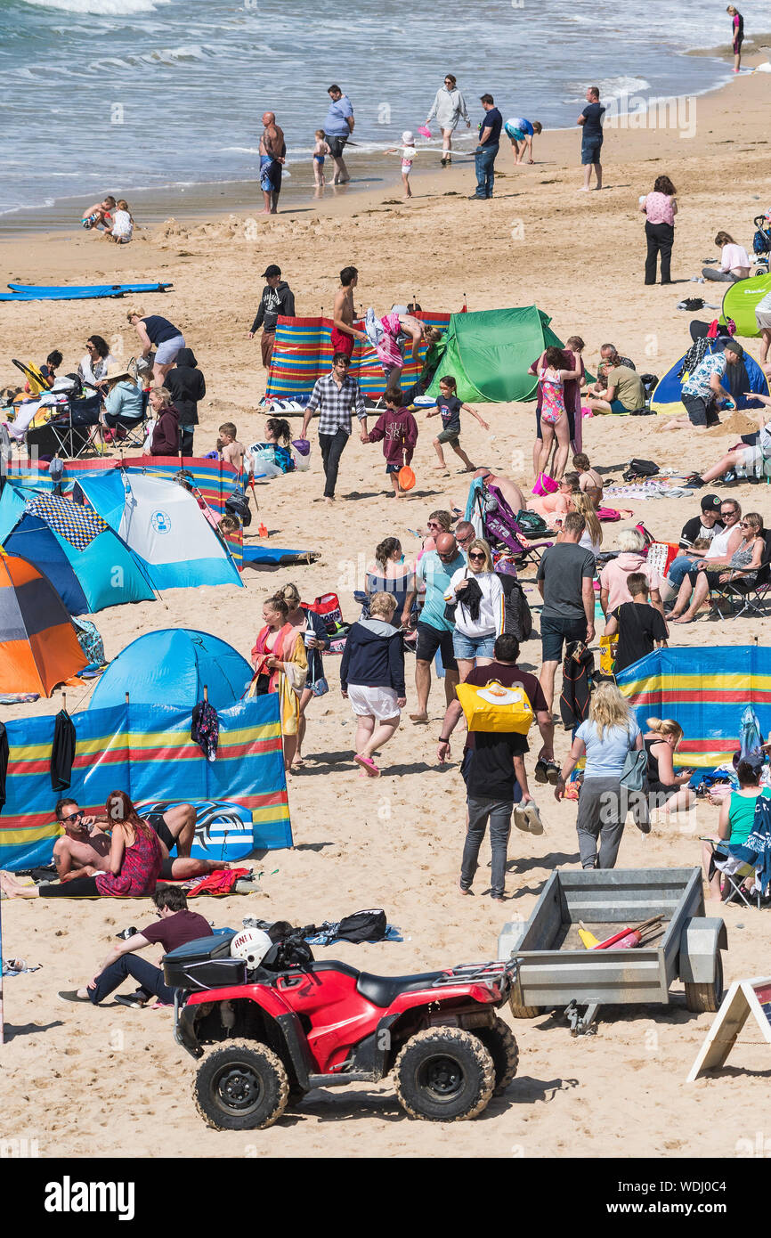 Holidaymakers on a staycation holiday enjoying themselves on Fistral Beach in Newquay in Cornwall. Stock Photo