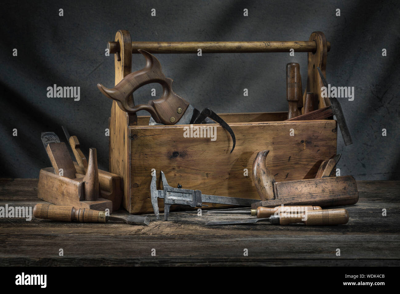 Still life - Old Wooden vintage toolbox with hammers, saw, chisels, plane and pliers in carpentry Stock Photo