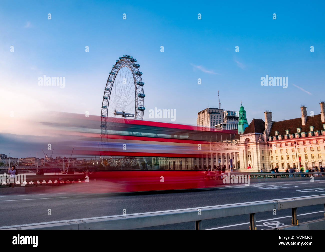 Long exposure photography of Double decker red bus in motion on Westminster Abbey bridge against the Eye of London in England Stock Photo