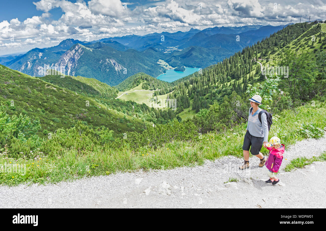 Mother With Daughter On Mountain Against Sky Stock Photo