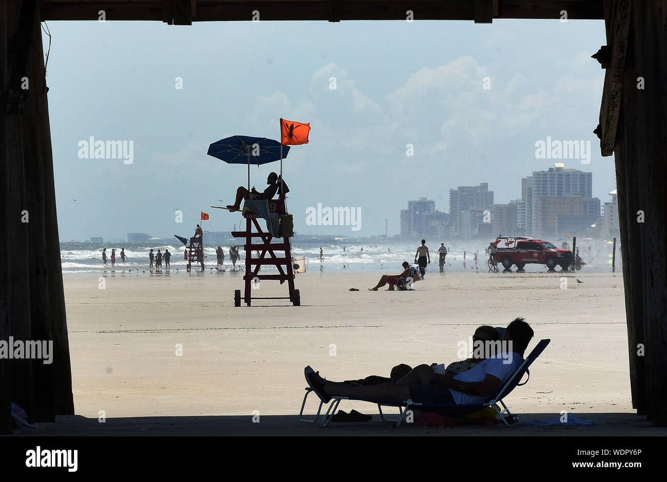 Titusville, FL, USA. 29th Aug, 2019. People relax at the shade under the Daytona Beach pier several days ahead of the Hurricane Dorian which is expected to become a Category 4 hurricane before making landfall in Florida on Labor Day. Credit: Paul Hennessy/SOPA Images/ZUMA Wire/Alamy Live News Stock Photo