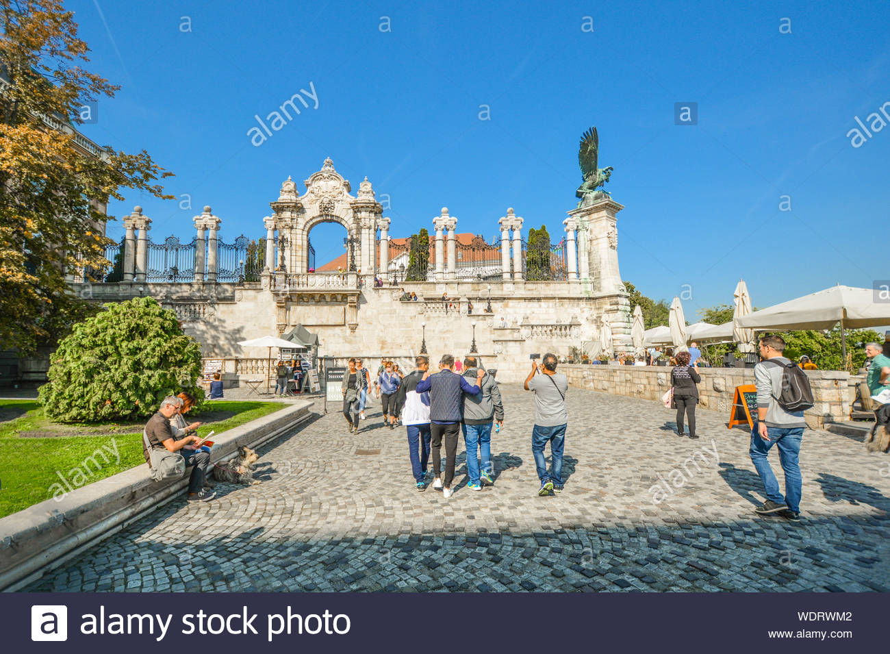 Tourists walk together and enjoy a sunny day in early autumn at the Buda Castle Hill District near the Turul bird statue in Budapest Hungary Stock Photo