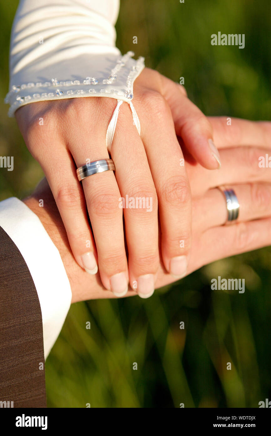 Cropped Hands Of Couple Showing Wedding Rings Stock Photo