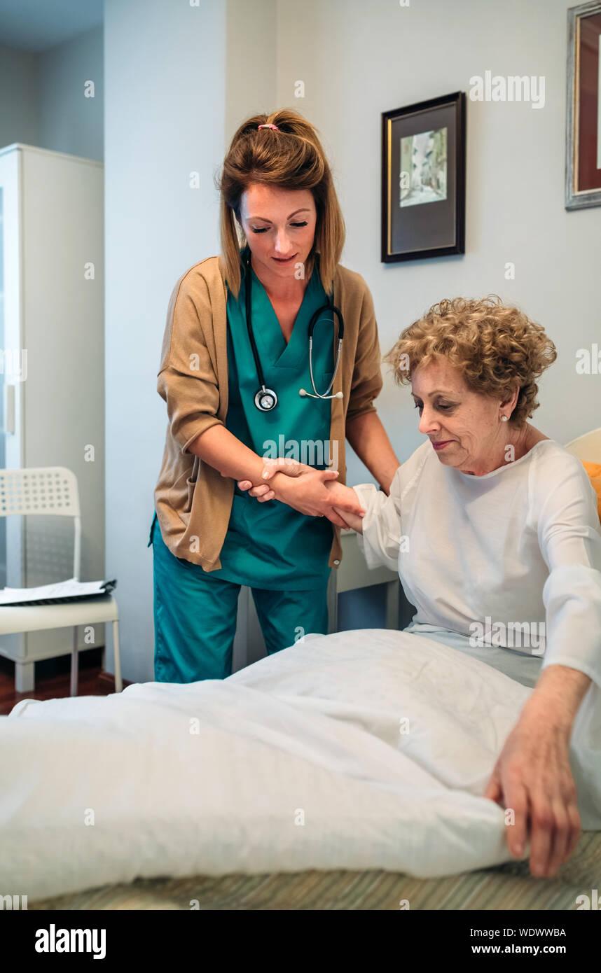 Nurse Caring Senior Patient In Hospital Stock Photo