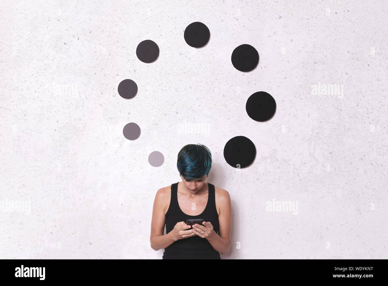 Woman Using Phone While Standing By Circular Shape Decorations On Wall Stock Photo