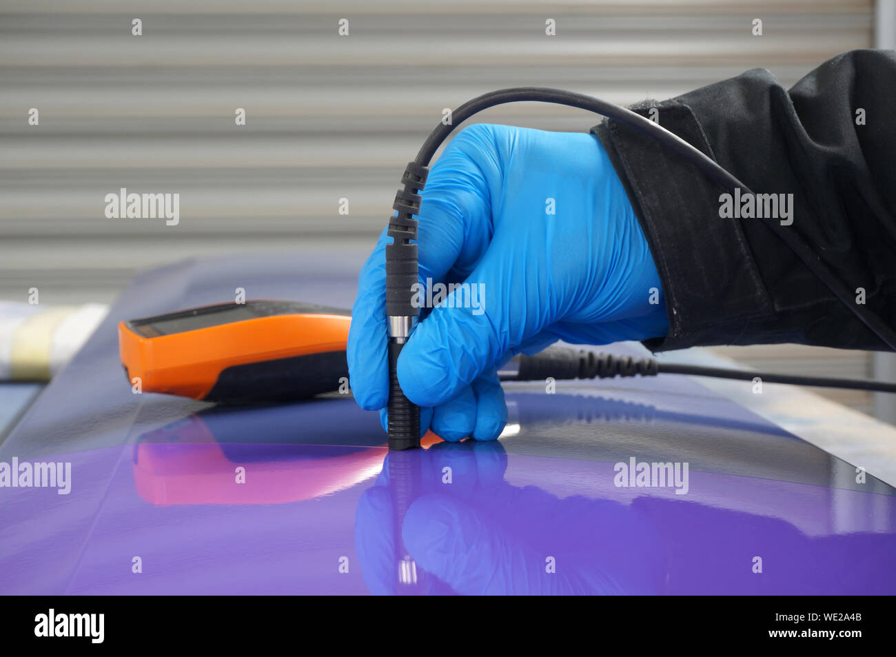Person using probe, with digital tester, to measure the paint thickness microns on a painted metal panel. Person wearing protective gloves. Stock Photo