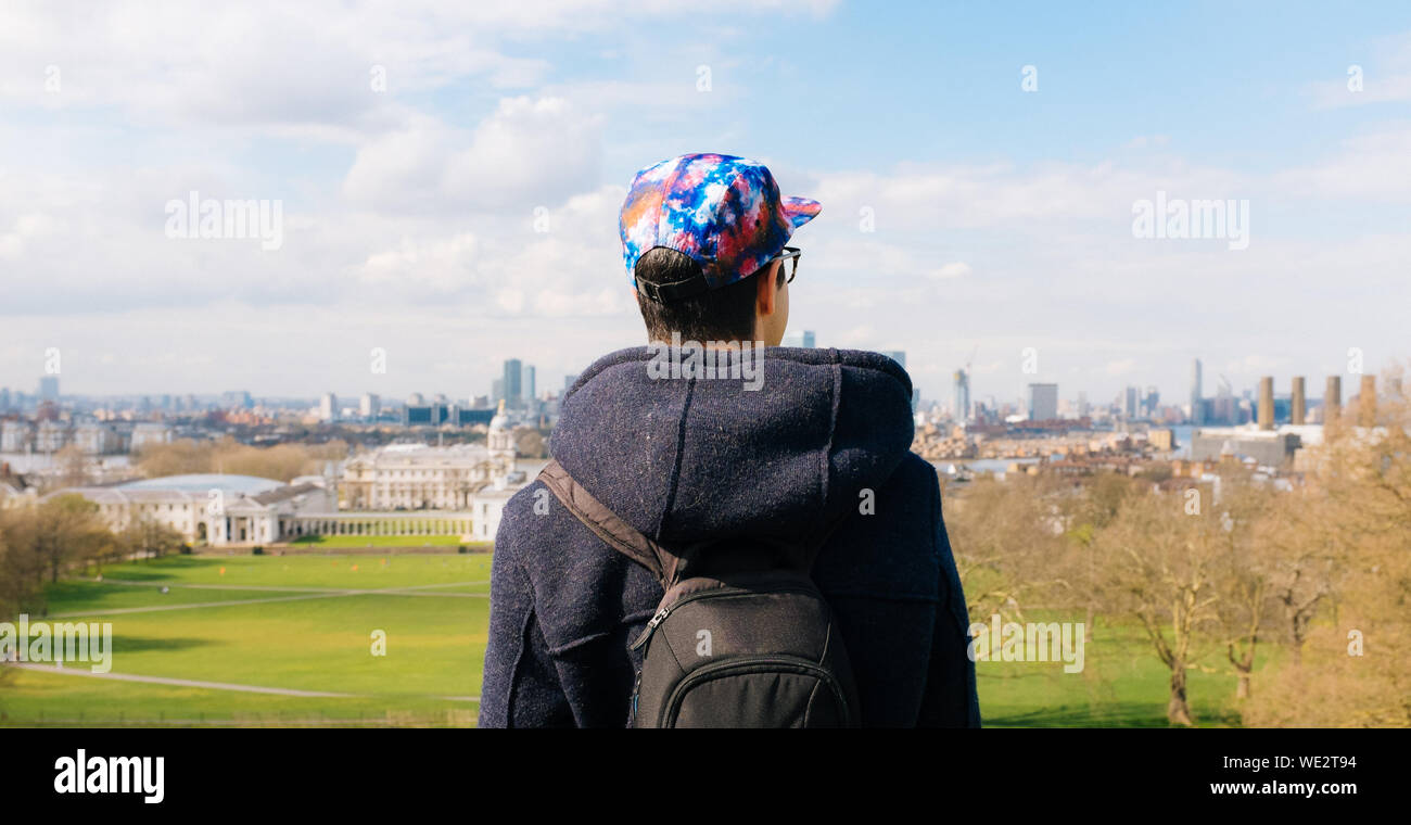 Rear View Of Man Wearing Cap While Standing Against Field In City Stock Photo