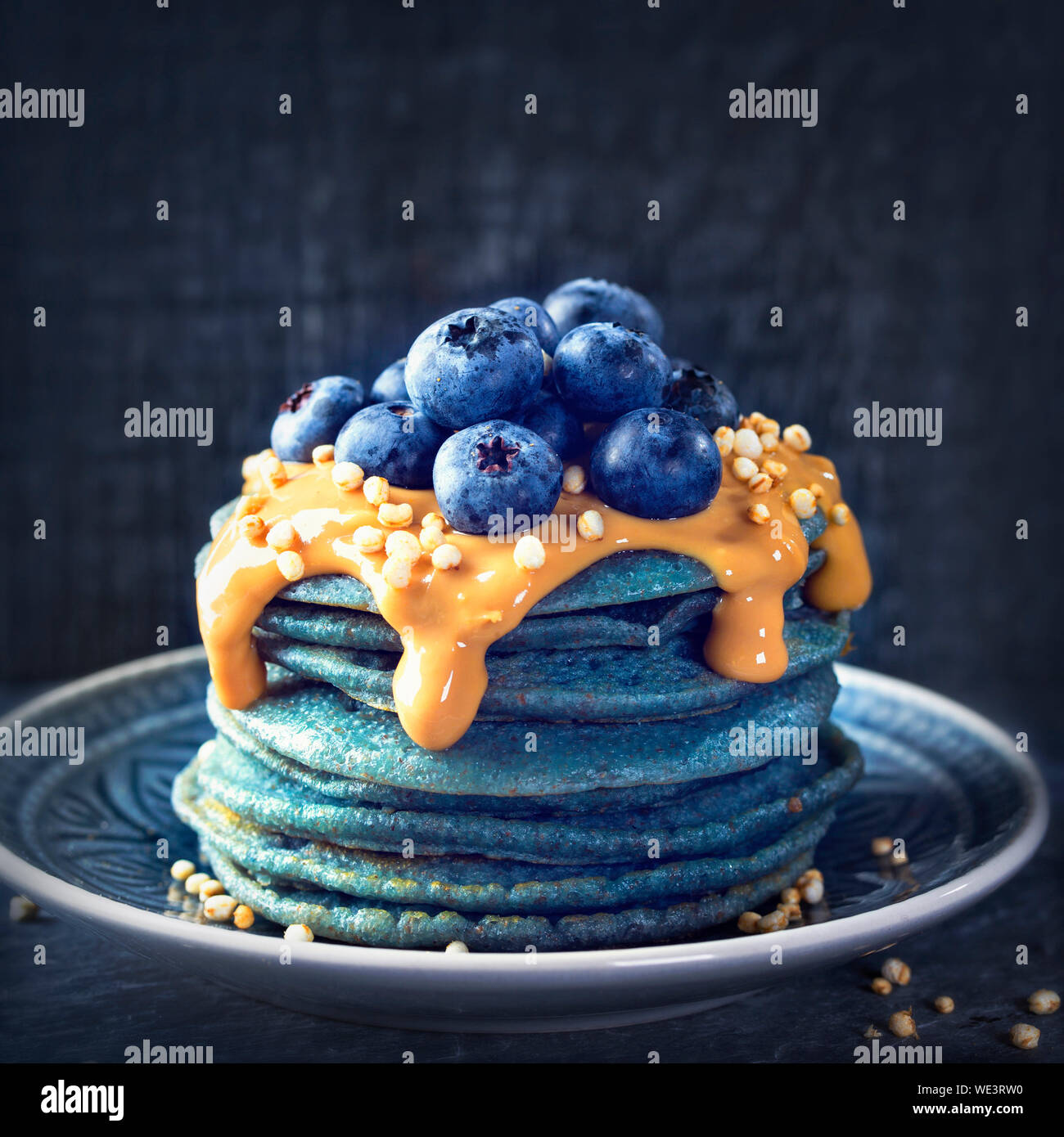 Blue spirulina pancakes topped with peanut butter, blueberries and popped quinoa Stock Photo