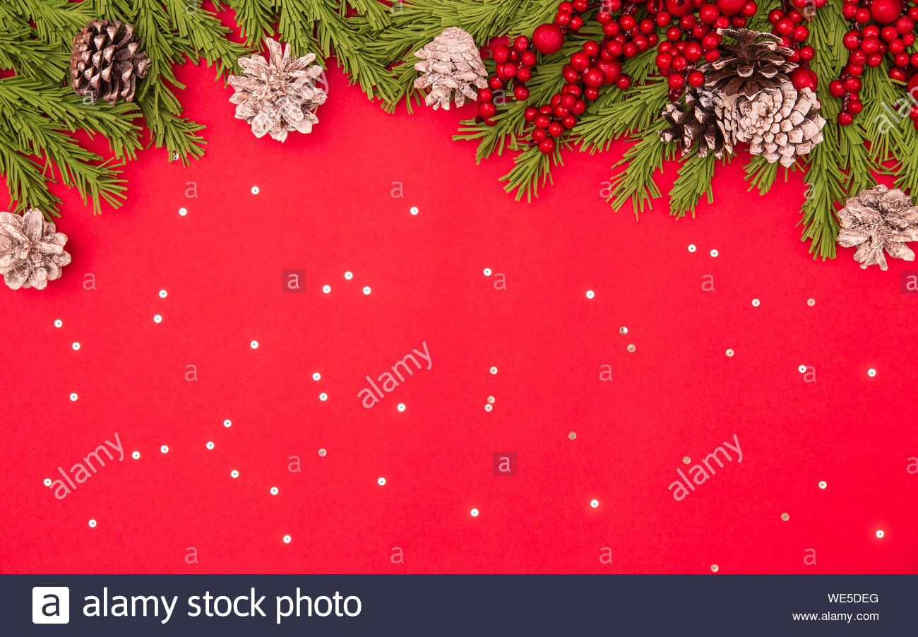 Christmas flat lay red background with fir branches, cones, holly berry, sparkles with copy space. Winter, New Year 2020, postcard, social media conce Stock Photo