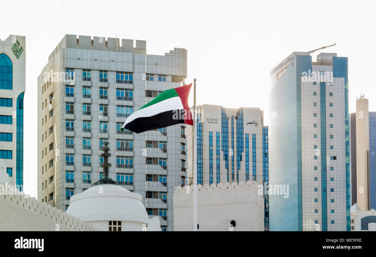 United Arab Emirates flags waving in the city at sunset Stock Photo