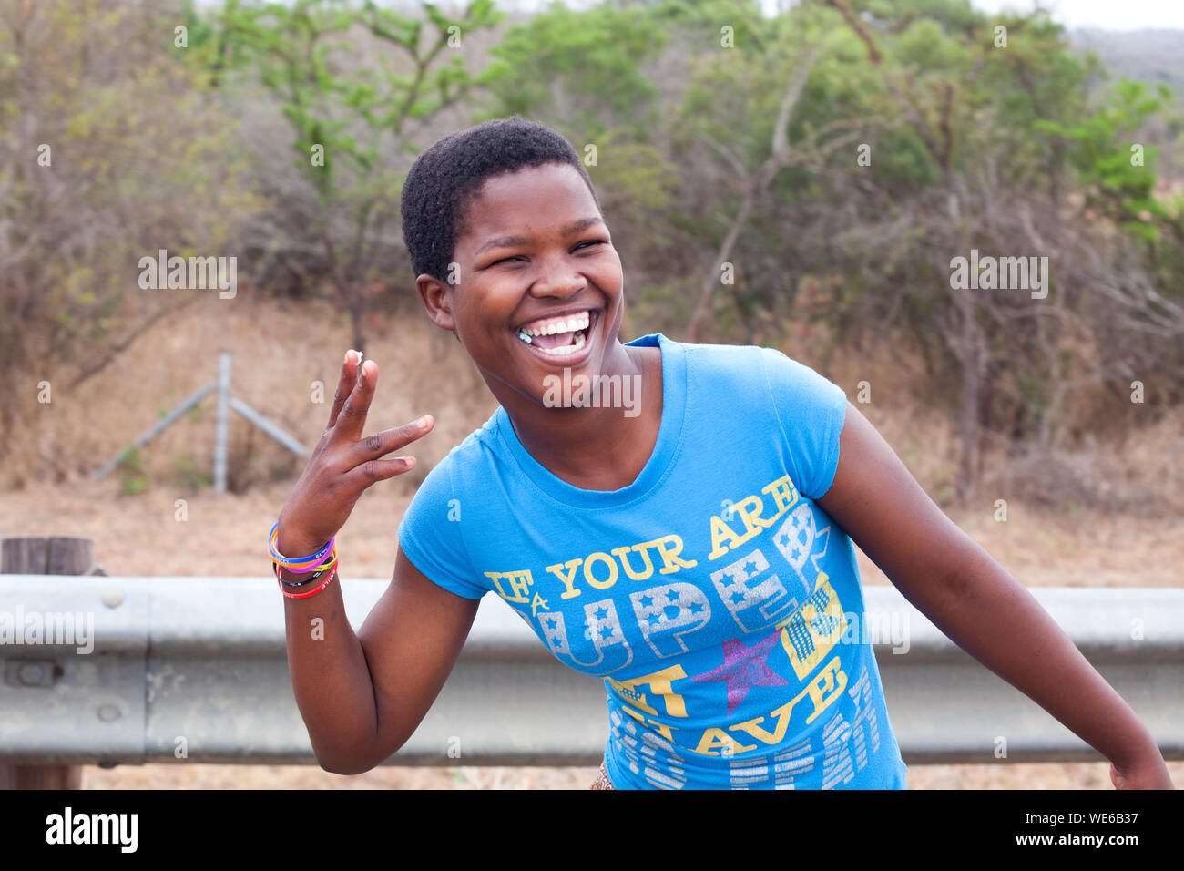 Mbabane, Swaziland - August 31, 2017: one happy african beautiful young girl in blue t-shirt smiling with white teeth and chewing gum outdoors closeup Stock Photo