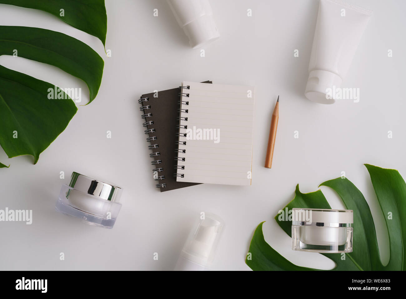 Directly Above Shot Of Spiral Notebook With Leaves And Beauty Products On Table Stock Photo