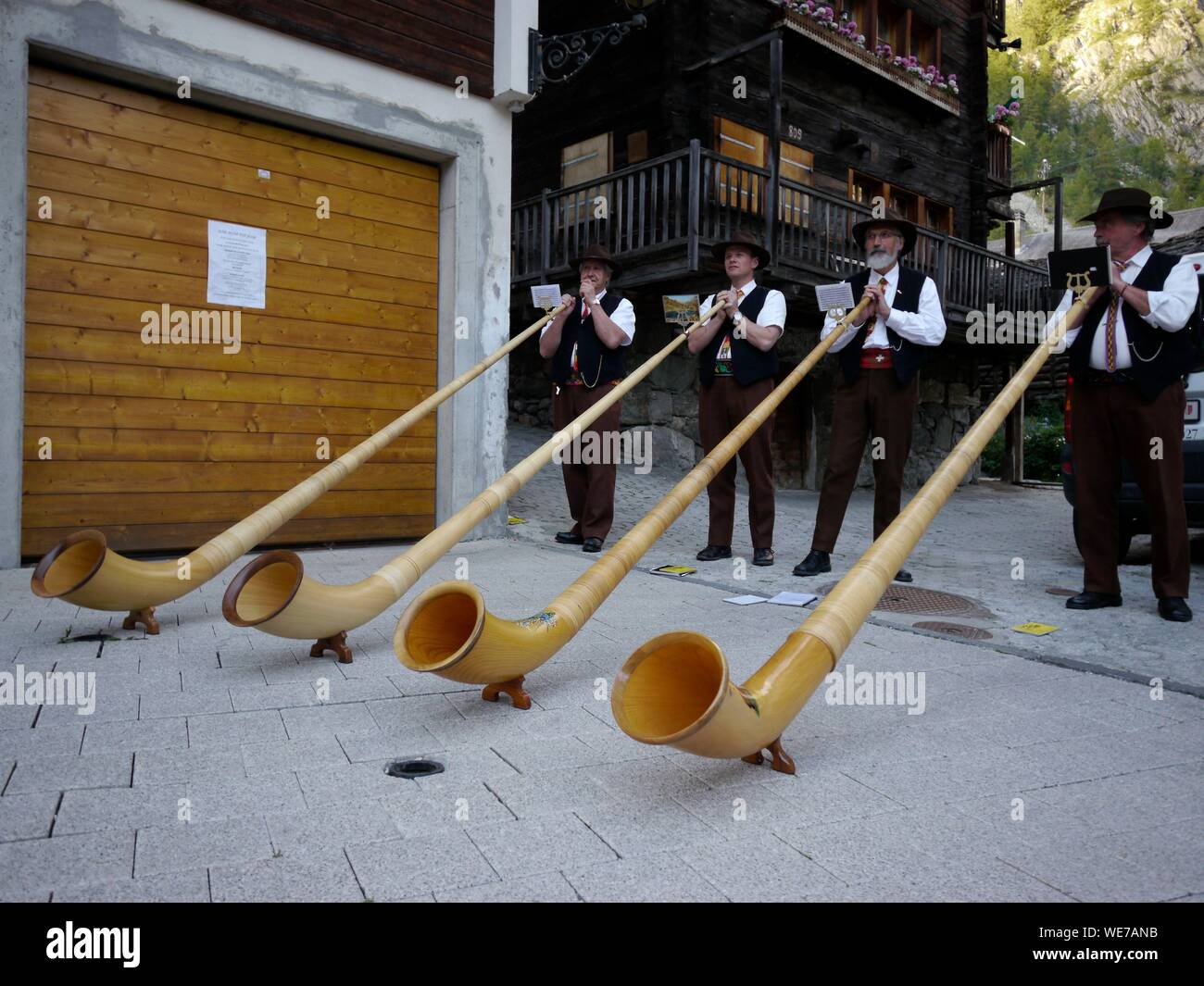 Switzerland, Valais Canton, Val d'Herens, village of Evolene, folkloric festival for the departure of herens black cows reines to the mountain grazing land (estive) in july, playing alpen horn Stock Photo