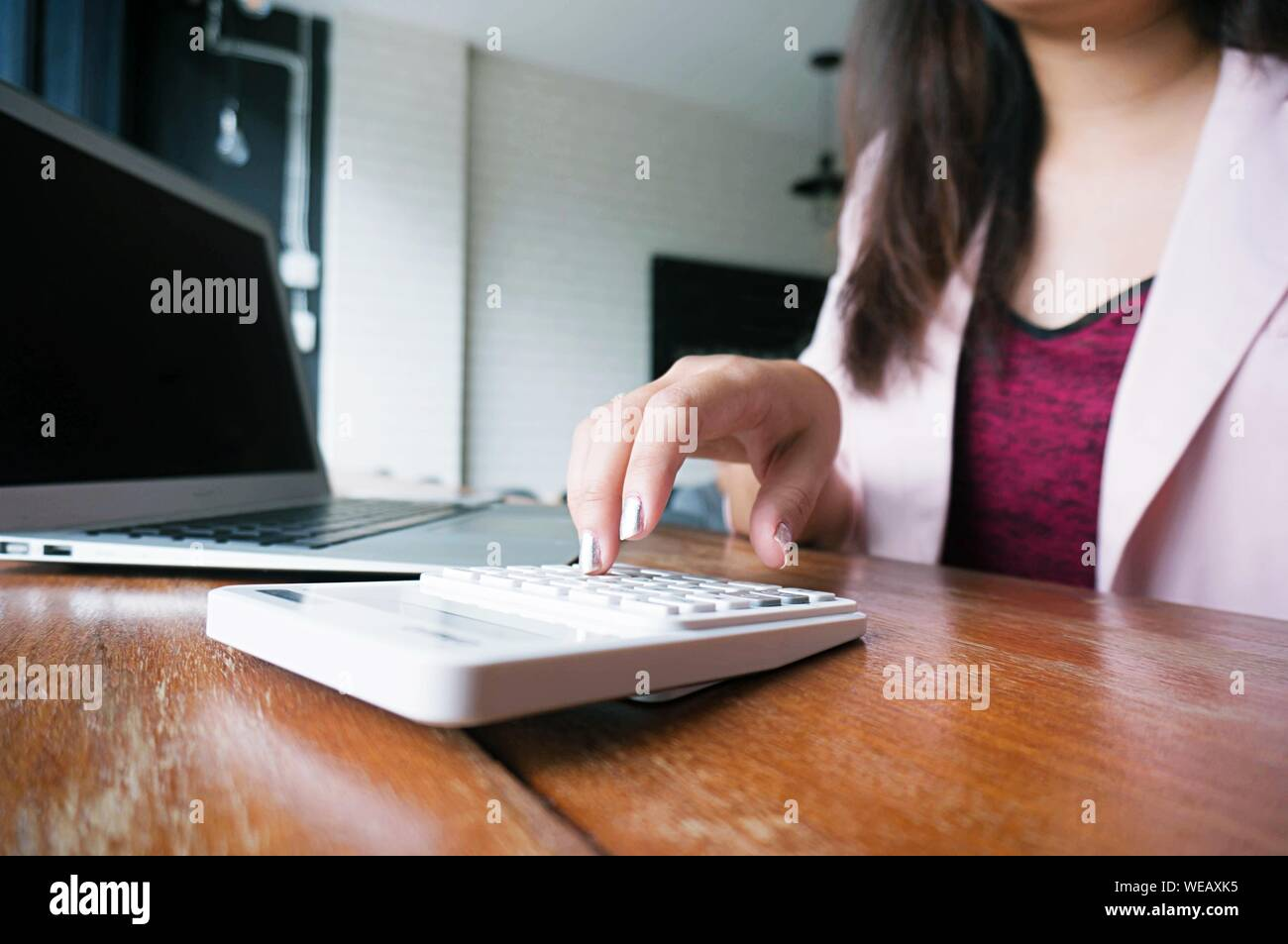 Midsection Of Businesswoman Using Calculator By Laptop While Working In Office Stock Photo