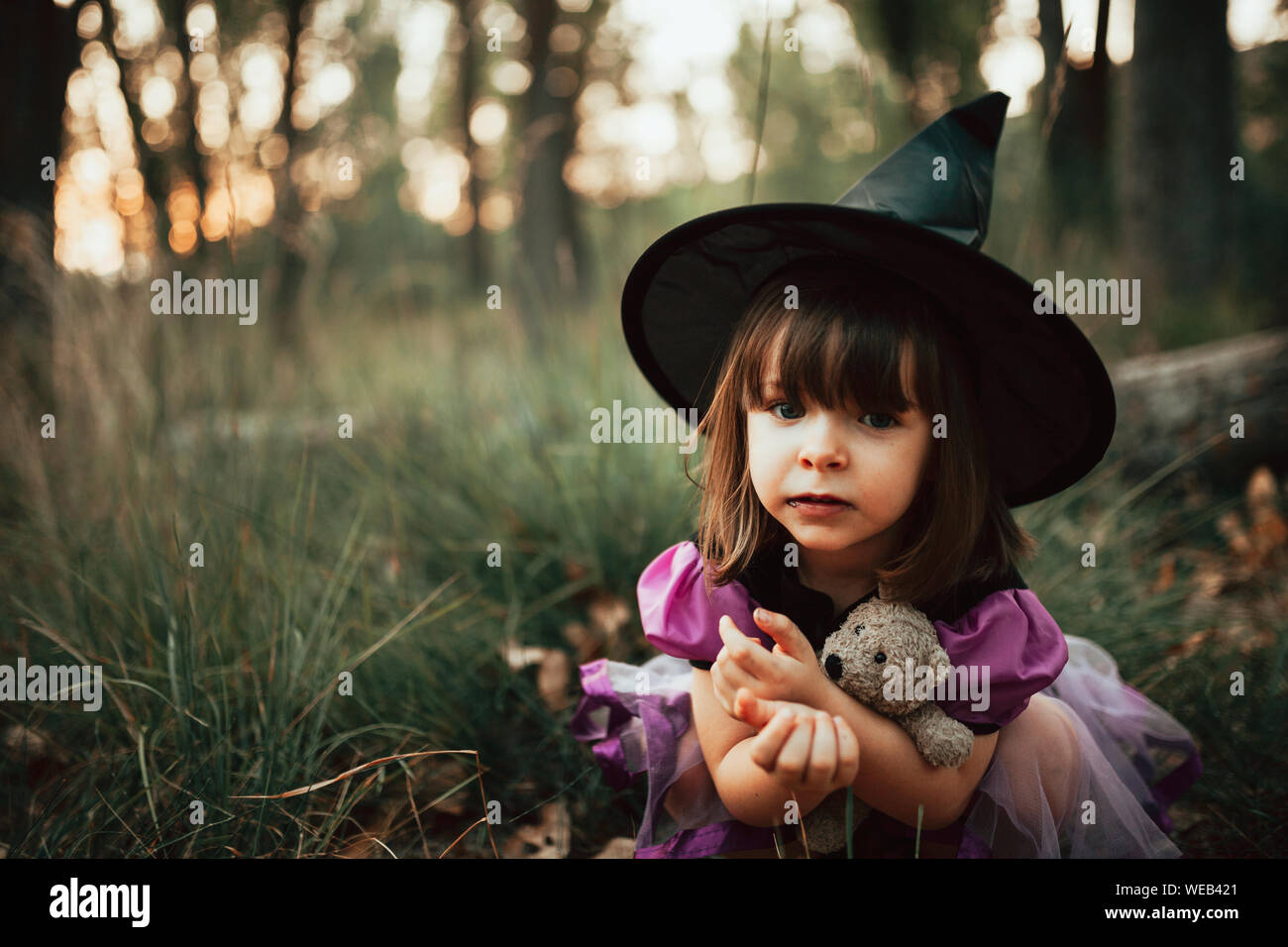 Smiling girl disguised as a witch in the woods during Halloween Stock Photo