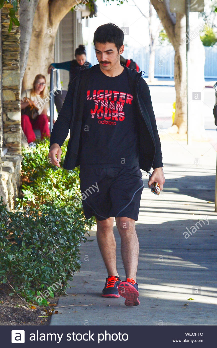 Los Angeles, CA - While Joe Jonas finished another workout session at his L.A. gym, his young brother Nick grabbed a to-go lunch not too far from there, Joe wore a new Adidas t-shirt advertising their new running shoes, black shorts and black and red Nike sneakers while his brother look a little more formal wearing a plaid shirt, black trousers and black leather boots. AKM-GSI December 10, 2013 Stock Photo