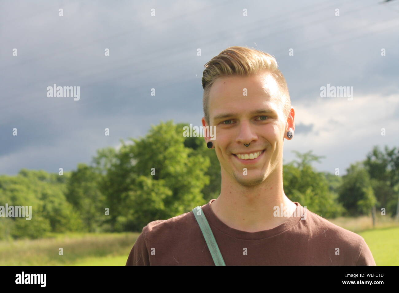 Portrait Of Young Man With Pierced Ears And Nose Against Sky Stock Photo