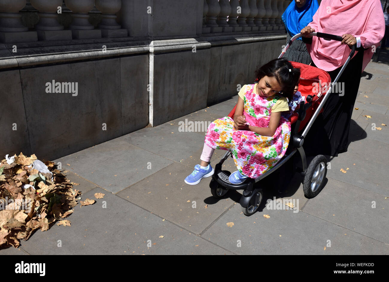 London, England, UK. Muslim faily - small girl in a pushchair Stock Photo