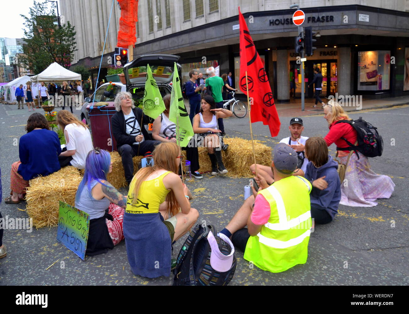 A group sits on straw bales outside Kendals store as Northern Rebellion protesters, part of the global movement Extinction Rebellion, blocked Deansgate and its side streets in central Manchester, uk, on 30th August, 2019 at the start of a four day protest. The protesters are demanding that the Government tells the truth about the climate emergency, takes action now, and is led by a citizens' assembly on climate change. Stock Photo
