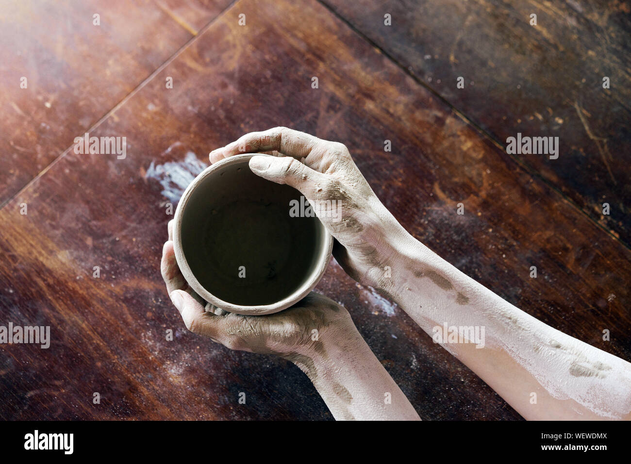 Female hands hold with a wet clay bowl. Pottery making Stock Photo