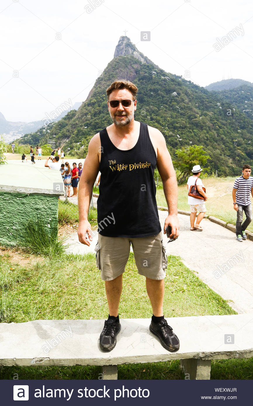 """Rio de Janeiro, Brazil - Russell Crowe is all smiles as he enjoys the view from Corcovado Mountain in Rio de Janeiro, Brazil. The actor is in town to promote his new flick """"Noah"""". Russell is clearly proud of his latest role, as he said his portrayal of the pre-Flood Patriarch will go against the grain of common belief. AKM-GSI March 21, 2014 Stock Photo"""