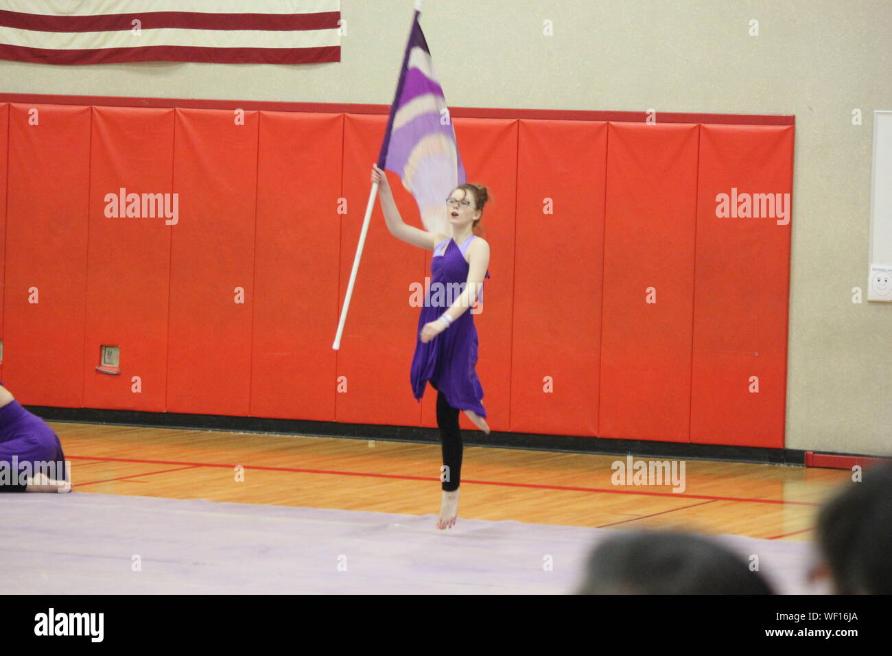 Ballet Dancer Holding Flag While Performing Winter Guard In Gymnasium Stock Photo