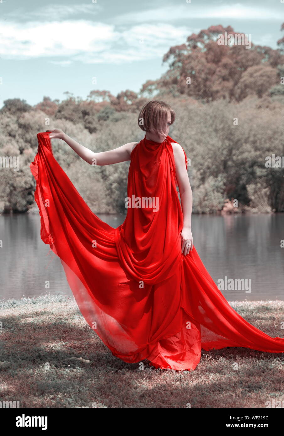 Woman Covered In Red Dress Standing At Lakeshore Stock Photo