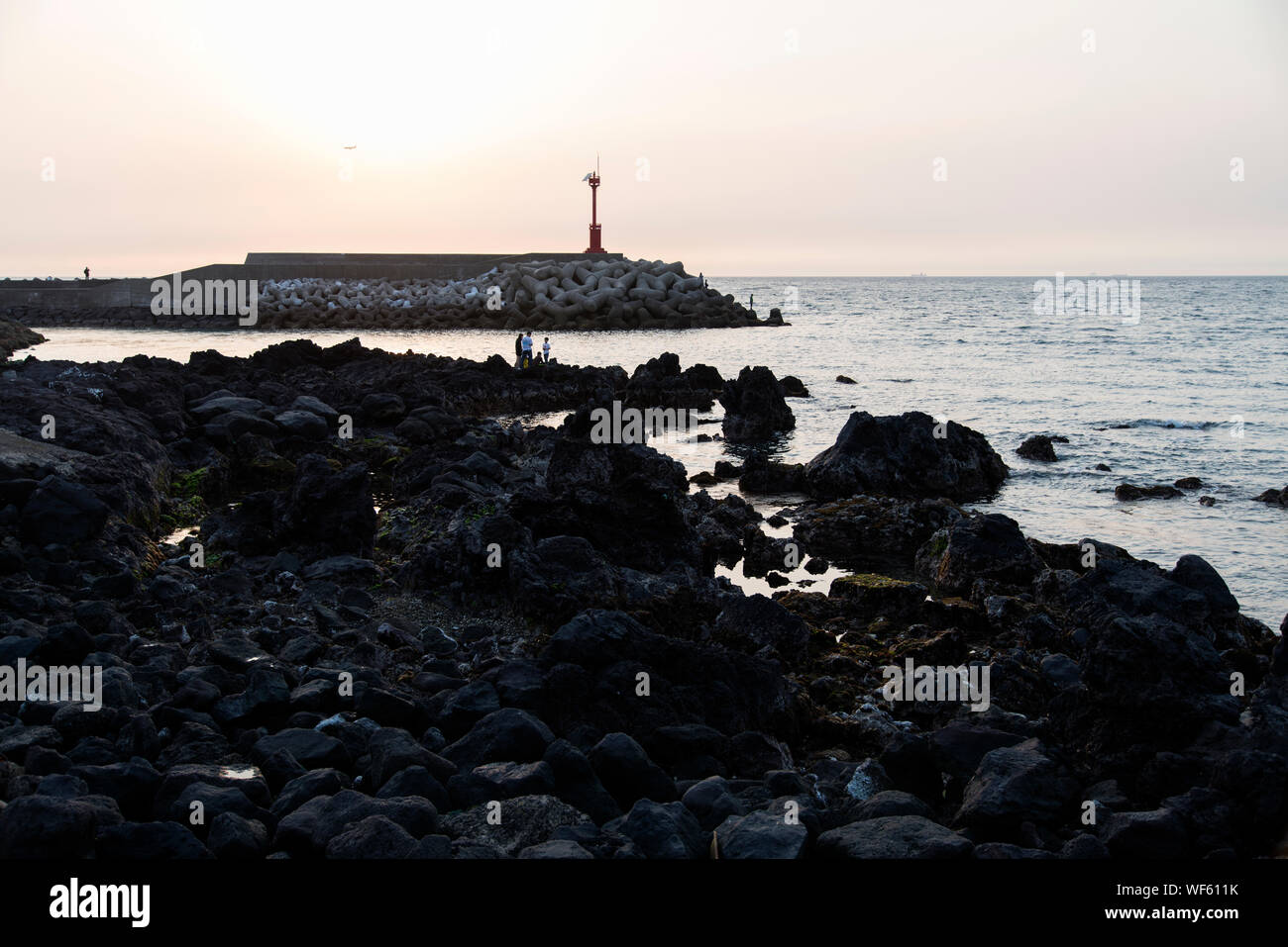 Rocky Shore Against Sky During Sunset - Stock Photo