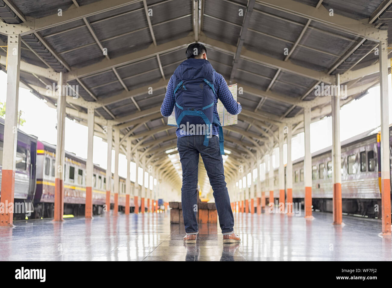 Full Length Of Tourist Reading Map While Standing At Railroad Station Platform Stock Photo