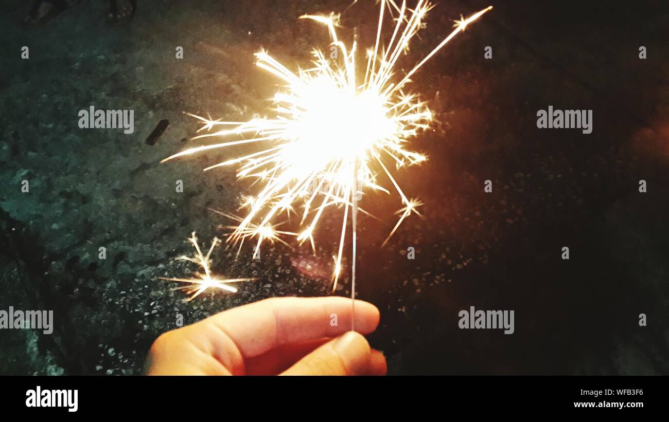Close-up Of Hand Holding Diwali Cracker Against Blurred Background Stock Photo