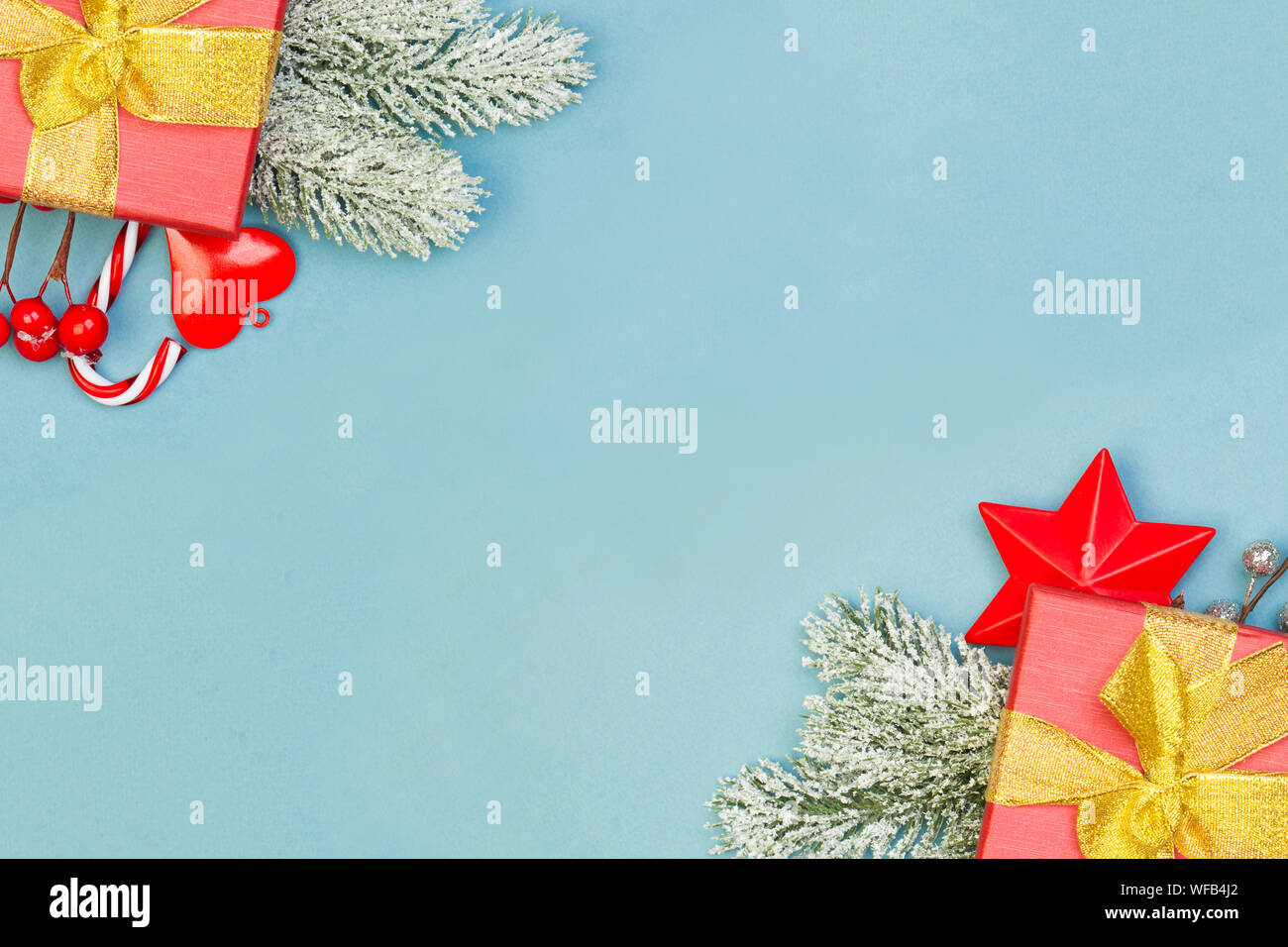 Christmas composition border with red gifts, holly berries and green fir branch on blue background Stock Photo