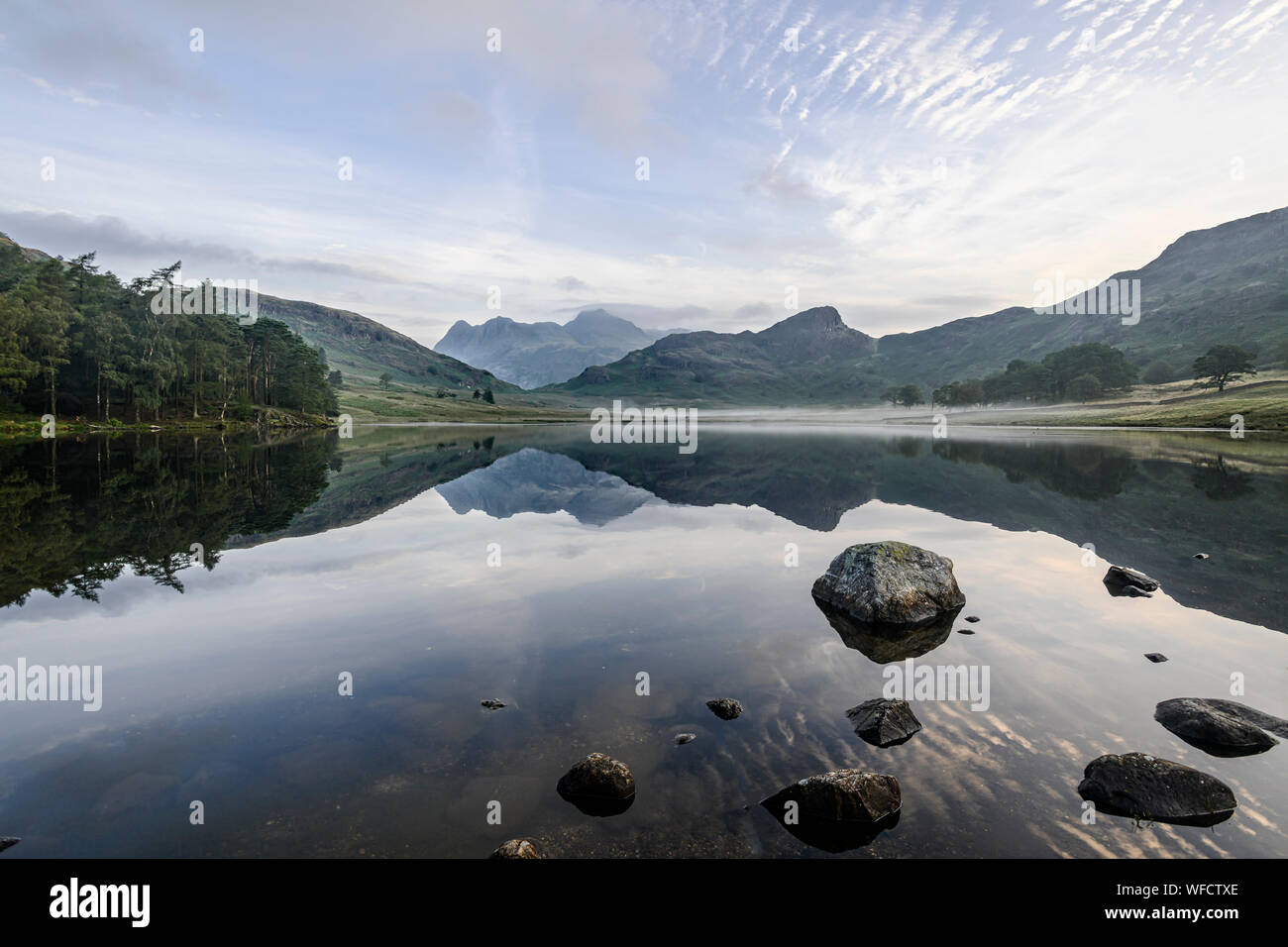 Mirror-like reflections of the Langdale Pikes in Blea Tarn early morning in late summer Stock Photo
