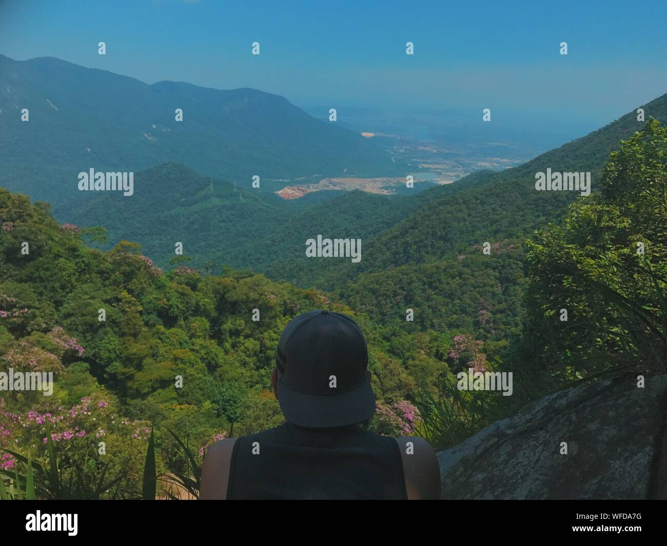 Rear View Of Man Wearing Cap Looking At Mountains Against Clear Blue Sky Stock Photo