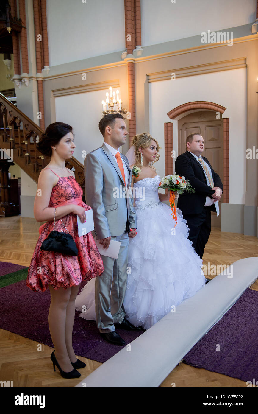 Young Couple Standing With Bridesmaid And Groomsman In Church Stock Photo