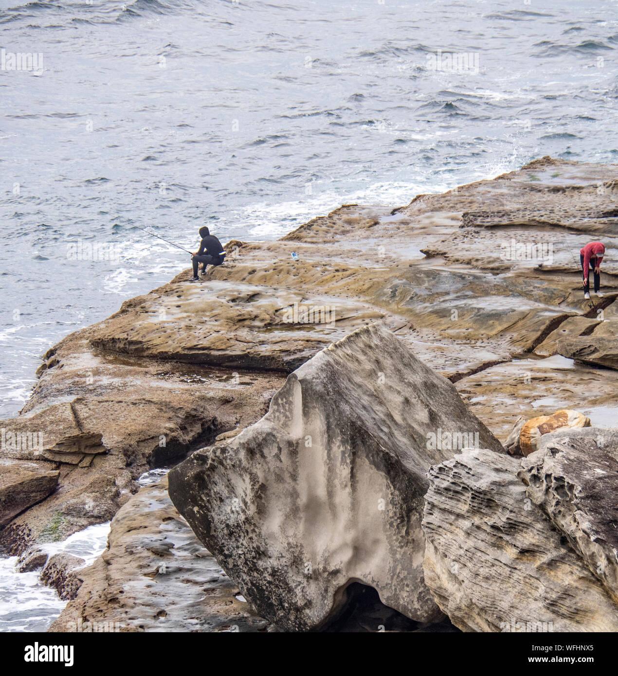 Two men rock fishing of rocks at Manly Headland Sydney NSW Australia. Stock Photo
