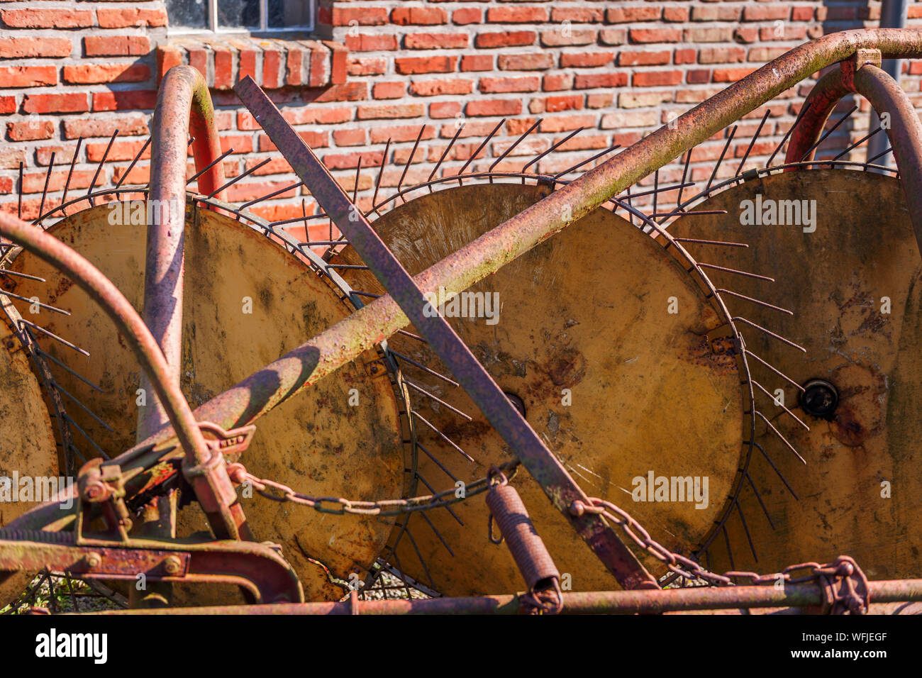 Closeup of an old, rusty tedder on a bricks wall. Stock Photo