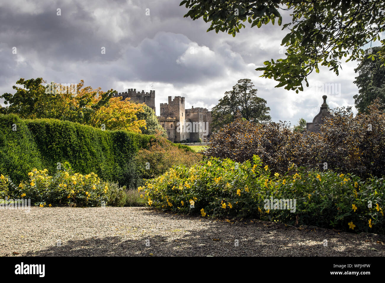 Raby Castle, Staindrop, Teesdale, County Durham, UK. 31st August 2019. UK Weather.  After a morning of sunny spells and showers the sun illuminates Raby Castle and its colourful gardens, which are starting to develop some autumnal colours.  Credit: David Forster/Alamy Live News Stock Photo